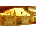 Skaidraus geltono gintaro gabalėlis su tvirtovės panorama