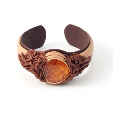 Kreminės spalvos apyrankė, puošta rudos odos ornamentu ir skaidriu konjakiniu gintaru