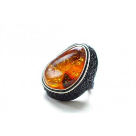 Juodos odos žiedas su šviesiai konjakiniu gintaru, įrėmintu baltos odos juostelėmis